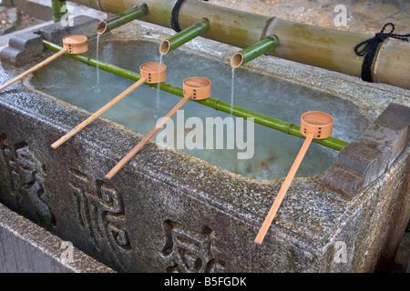 Bambus-Schöpfkellen ruht auf Hishaku Rack über eine rituelle Waschung Wassertrog Chuzua bei Yasaka Shinto Schrein - Stockfoto