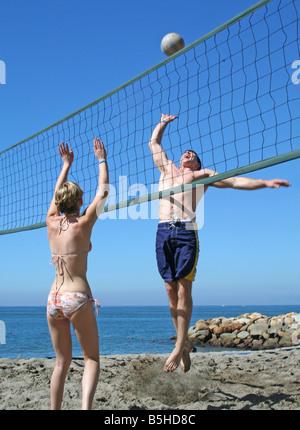 Junge Menschen, die am Strand Volleyball spielen - Stockfoto