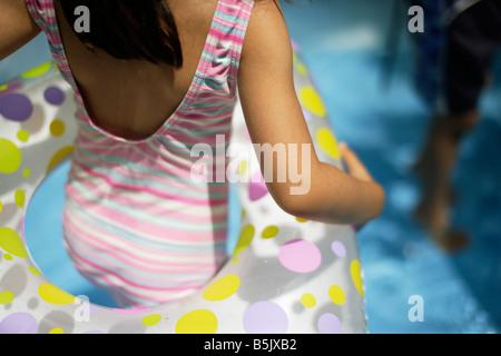 Fünf Jahre altes Mädchen im Planschbecken mit aufblasbaren Gummiring - Stockfoto
