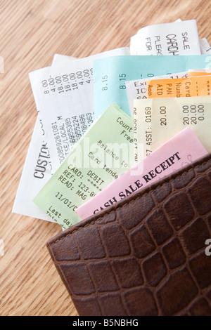 Braune Leder-Portemonnaie mit Quittungen auf hölzernen Theke gefüllt - Stockfoto