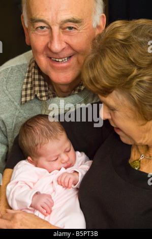 Vertikale Studioportrait stolze Großeltern ihr neugeborenes Baby Enkelin kuscheln. - Stockfoto