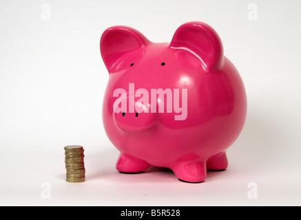 halbe Seitenprofil einer rosa Piggy Bank mit einem Haufen oder Stapel von Pfund-Münzen sitzen davor auf einem weißen - Stockfoto