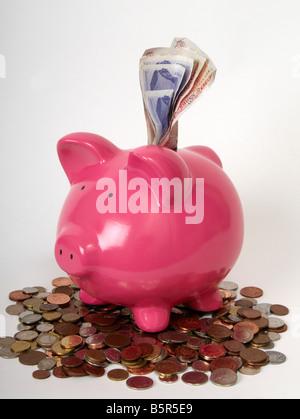 Rosa Sparschwein sitzt auf einem Stapel von Münzen mit britischen Banken Hinweis oben herausragen. - Stockfoto