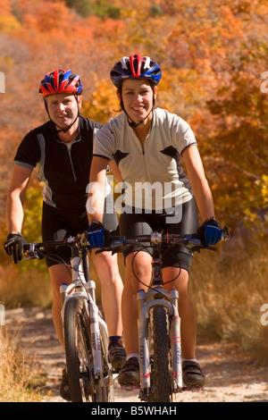 Junges Paar Mountain Bike Reiten inmitten der herbstlichen Farben auf dem Tempel-Steinbruch-Trail in Little Cottonwood - Stockfoto