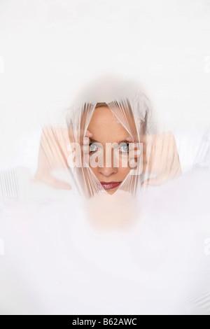Junge Frau reißt ein Loch in eine Plastikfolie, durchsehen - Stockfoto