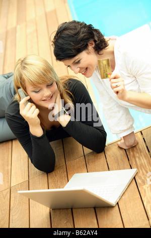 Zwei Frauen neben einem Schwimmbad mit einem Laptop auf einem Handy reden halten eine Kreditkarte in der Hand, bargeldloses - Stockfoto