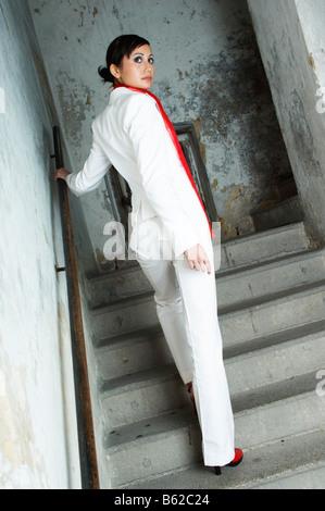 Junge Frau auf der Flucht in einem Treppenhaus - Stockfoto