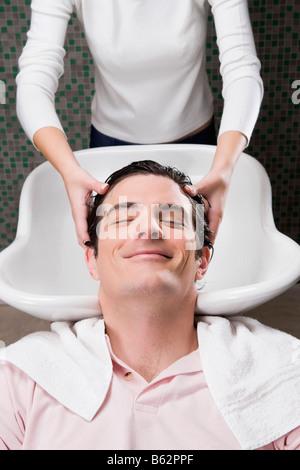 Mitte erwachsener Mann dass ein Haar in der Friseursalon waschen - Stockfoto