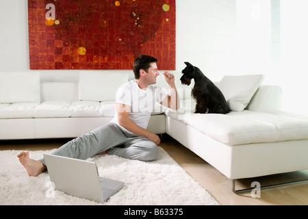 Mitte erwachsenen Mannes auf Teppich sitzen und spielen mit Hund - Stockfoto