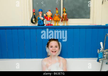 Zehn Jahre altes Mädchen in der Badewanne glücklich lächelnd, frech und niedlich mit seifigen Luftblasen wie einen - Stockfoto