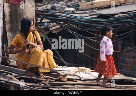 Eine Frau kämmt ihr Haar während der Sitzung in unter die vielen Stromkabel Fütterung ein Slum Kolkata Indien - Stockfoto