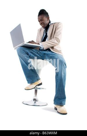 Ein junger afrikanischer Amerikaner Mann arbeitet auf dem Laptopcomputer - Stockfoto