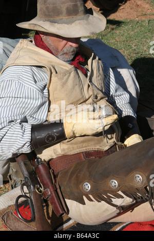 Ein Oldtimer Cowboy lehnte sich gegen seinen Pack und Sattel neben den Planwagen überprüft seine Taschenuhr - Stockfoto