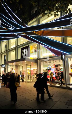 Käufer außerhalb der Lücke Mode speichern Oxford Street London Nacht zu Weihnachten - Stockfoto