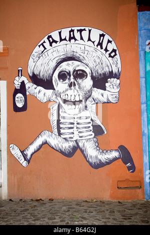 Oaxaca, Mexiko. Tag der Toten. Wandmalerei der laufenden Skelett Holding eine Flasche Mezcal, eine lokale alkoholische - Stockfoto