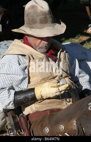 Ein Oldtimer Cowboy gelehnt sein Rudel überprüft seine Taschenuhr - Stockfoto