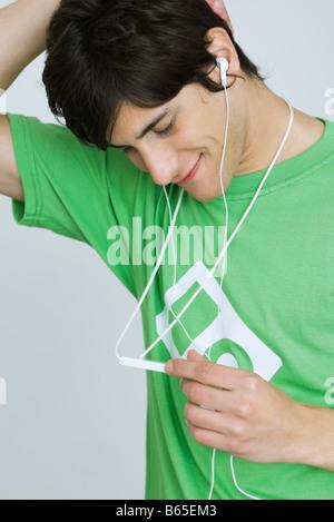 Junger Mann anhören von MP3-Player, Lächeln, Blick nach unten - Stockfoto