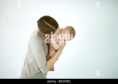 Mutter küssen Kleinkind auf die Wange, Baby nach unten - Stockfoto
