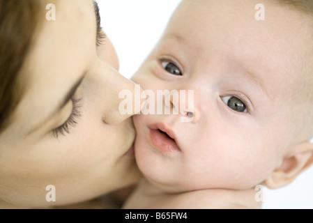 Mutter küssen Kleinkind auf die Wange, Baby, Blick in die Kamera - Stockfoto