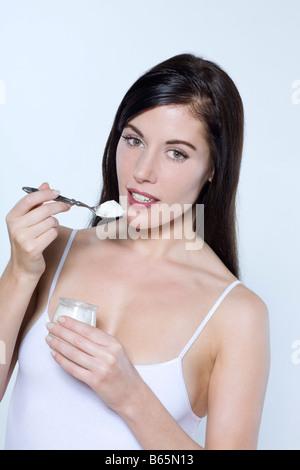 schöne junge Frau auf isolierte Hintergrund Essen Joghurt - Stockfoto