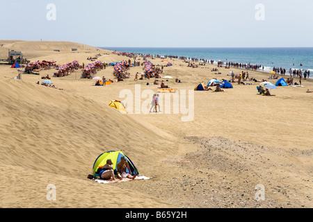 Massen von Menschen, die zum Sonnenbaden am Strand von Maspalomas Gran Canaria Spanien - Stockfoto