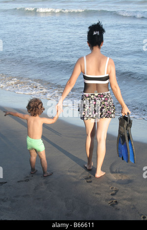 Eine Frau und ihr Sohn zu Fuß am Strand mit Schnorcheln flossen - Stockfoto