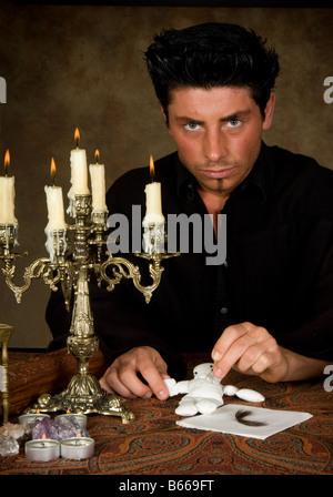 Mann stecken Nadeln in eine Voodoo-Puppe in der Nähe einer Haarlocke seines Opfers - Stockfoto