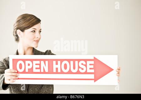Eine Frau mit einem Tag der offenen Tür-Schild - Stockfoto
