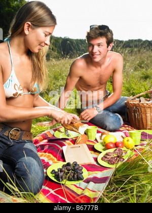 Paar mit einem Picknick in einem Feld - Stockfoto