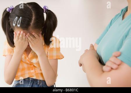 Nahaufnahme eines Mädchens versteckt ihr Gesicht und ihre Großmutter, die neben ihr Stand - Stockfoto
