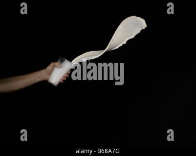 Mann wirft weiße Flüssigkeit aus einem Glas - Stockfoto