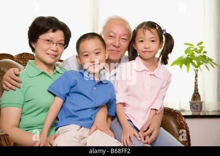 Porträt von ein älteres Paar sitzt mit ihren Enkelkindern - Stockfoto