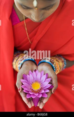 Indische Frau bietet eine Nymphaea tropische Seerose Blume in ihrer hohlen Hand. Andhra Pradesh, Indien - Stockfoto