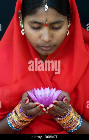 Indische Frau bietet eine Nymphaea tropische Seerose Blume in einem roten Sari.  Andhra Pradesh, Indien - Stockfoto