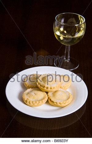 Ein Teller mit hausgemachten Mince Pies und ein Glas Weißwein. - Stockfoto