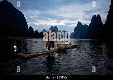 Fischer, stehend auf einem hölzernen Floß in einem Fluss, Li-Fluss, XingPing, Yangshuo, Provinz Guangxi, China - Stockfoto