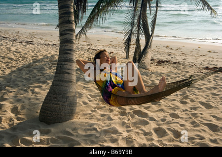 Mexiko, Tulum, Quintana Roo Tourist (Frau) in der Hängematte unter Palmen am Strand - Stockfoto
