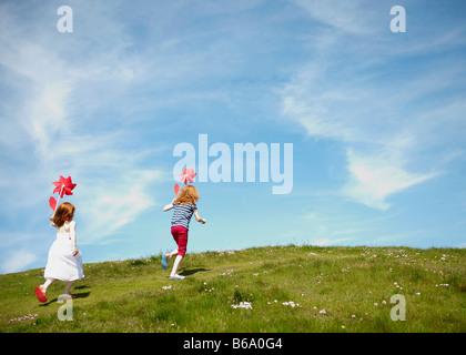 2 Mädchen laufen in Feld mit Windmühlen - Stockfoto