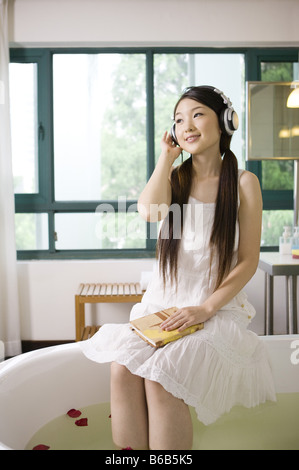 Junge Frau trägt den Kopfhörer und amüsiert sich - Stockfoto