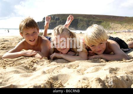 Drei Kinder liegen am Strand - Stockfoto