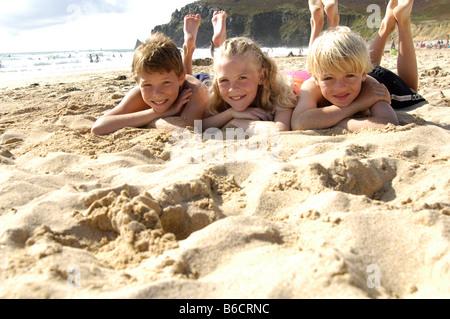 Porträt von drei Kindern am Strand liegen und lächelnd - Stockfoto