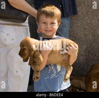 Kleiner Junge hilft Papa auf dem Bürgersteig in Brighton Beach Brooklyn Welpen zu verkaufen - Stockfoto