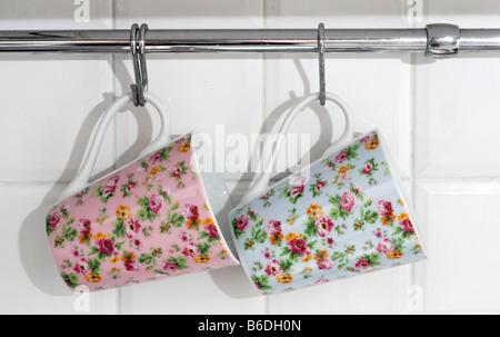 Floral Dekorierte Tassen Hängen An Haken In Der Küche Stockfoto