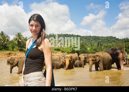 Ein Tourist, posiert für ein Foto vor Elefanten am Maha Oya Fluss in der Nähe von The Pinnawela-Elefantenwaisenhaus - Stockfoto