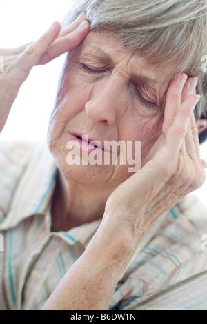 Frau drücken ihre schmerzenden Tempel - Stockfoto