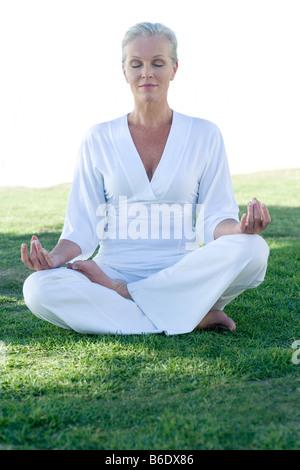Meditation. Frau sitzt im Lotussitz. - Stockfoto
