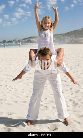 Vater und Tochter. Mann mit seiner Tochter auf dem Rücken am Strand. - Stockfoto