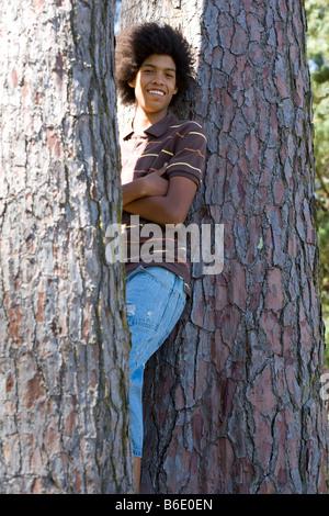 Teenager an einen Baum gelehnt - Stockfoto