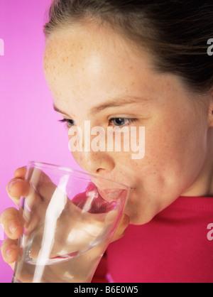 Trinken von Wasser. 8 Jahre altes Mädchen trinken ein Glas Wasser. - Stockfoto