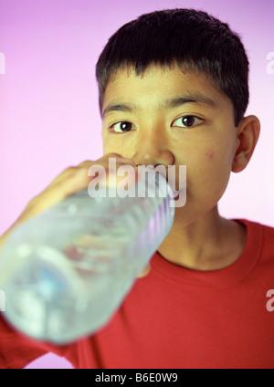 Trinken von Wasser. 9-Year-Old Boy trinken aus einer Flasche Wasser. - Stockfoto